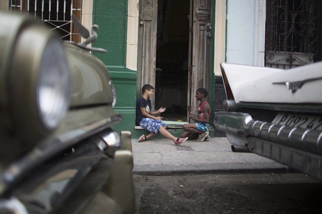 Cristian Daguada, 11 (L), plays futbolito, or little soccer in Spanish, with his neighbour Brian Meson, 11, in downtown Havana, March 12, 2015. (Photo by Alexandre Meneghini/Reuters)