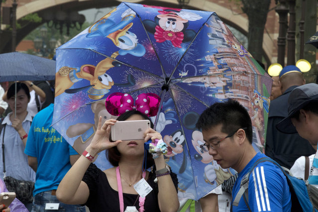 A woman takes photo on her phone during the opening day of the Disney Resort in Shanghai, China, Thursday, June 16, 2016. (Photo by Ng Han Guan/AP Photo)