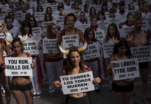 """Anti-bullfighting demonstrators protest against the bull runs dressing in the typical white and red colors while displaying banners which read, """"You Run. Bulls Die"""", on the Ayuntamiento Square in Pamplona northern Spain, Saturday, July 5, 2014. On July 6, the San Fermin festival will begin with the """"txupinazo"""", the opening ceremony with people participating in bull runs, music and dance, through the old street of the city. (Photo by Alvaro Barrientos/AP Photo)"""