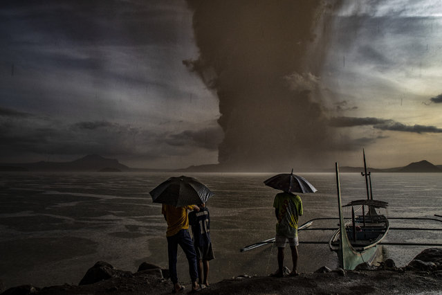 "Residents look on as Taal Volcano erupts on January 12, 2020 in Talisay, Batangas province, Philippines. Local authorities have begun evacuating residents near Taal Volcano as it began spewing ash up to a kilometer high Sunday afternoon. The Philippine Institute of of Volcanology and Seismology has raised the alert level to three out of five, warning of the volcano's continued ""magmatic unrest"". (Photo by Ezra Acayan/Getty Images)"