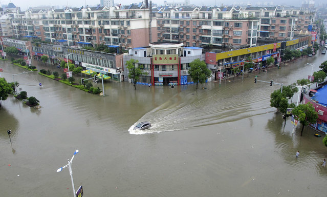 A car travels on a flooded street after heavy rainfalls hit Ruichang, Jiangxi province July 5, 2014. The Chinese National Meteorological Center (NMC) issued a yellow alert on Saturday morning, saying heavy rains and strong winds will hit parts of eastern and central China over the weekend, Xinhua News Agency reported. (Photo by Reuters/Stringer)