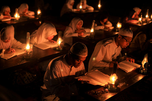 "Students read the Koran outdoors by oil lamp to celebrate ""Nuzul al-Koran"" or ""The Revelation of the Koran"", on the 17th day of the holy month of Ramadan that the first verse of the Koran was revealed to Prophet Muhammad, in Solo, Central Java, Indonesia June 21, 2016 in this photo taken by Antara Foto. (Photo by Maulana Surya/Reuters/Antara Foto)"