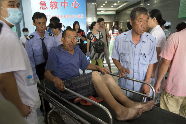 A man is pushed through an emergency ward at a hospital receiving victims of an explosion in northeastern China's Tianjin municipality, Thursday, August 13, 2015. (Photo by Ng Han Guan/AP Photo)