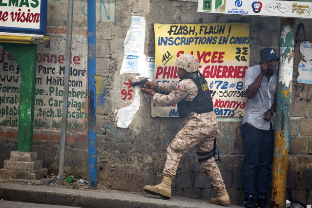 A police officer points his gun at residents of Delmas 95 district during a protest to demanding the resignation of Haiti's president Jovenel Moise in Port-au-Prince, Haiti, Monday, November 18, 2019. At least four people were shot and wounded during a small protest in Haiti's capital after a speech by embattled President Jovenel Moise. A local journalist, a police officer and two protesters were rushed away with apparent bullet wounds. (Photo by Dieu Nalio Chery/AP Photo)