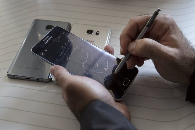 A man writes on a Samsung Galaxy Note 5 at the product's launch event in New York August 13, 2015. Samsung Electronics Co Ltd unveiled a new Galaxy Note phablet and a larger version of its curved-screen S6 edge smartphone on Thursday, marking a fresh bid by the South Korean tech giant to revive momentum in its handset business. (Photo by Andrew Kelly/Reuters)