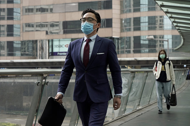 A man wearing protective face mask, walks on a street in the Central, the business district in Hong Kong, Wednesday, February 12, 2020. China on Wednesday reported another drop in the number of new cases of a viral infection and 97 more deaths, pushing the total dead past 1,100 even as the country remains largely closed down to prevent the spread of the disease. (Photo by Kin Cheung/AP Photo)