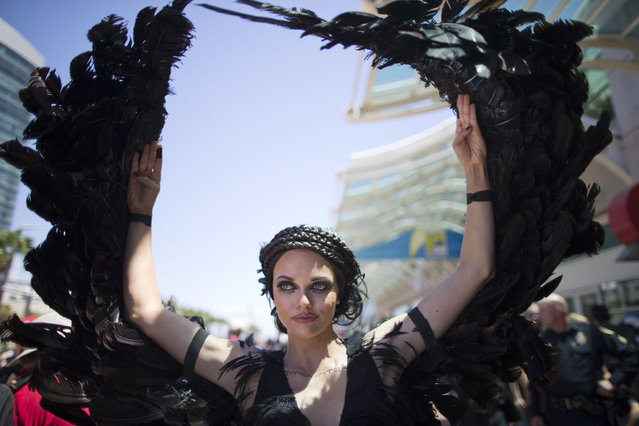 "A woman dressed as the character Katniss Everdeen from the movie, ""The Hunger Games: Catching Fire"", poses in front of Comic-Con Thursday, July 24, 2014, in San Diego. (Photo by AP Photo)"