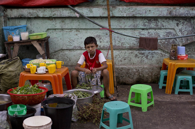 A boy cleans vegetables at a street-side restaurant in Yangon, Myanmar, Wednesday, May 11, 2016. The International Monetary Fund (IMF) forecasts Myanmar's economic growth at 8.5 percent in 2016. (Photo by Gemunu Amarasinghe/AP Photo)