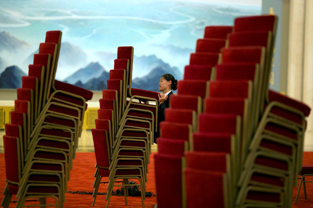 A worker piles up chairs at the end of the Greece-China Maritime Cooperation to Fuel Growth Bilateral Business Forum held at the Great Hall of the People in Beijing, China, July 4, 2016. (Photo by Ng Han Guan/Reuters)