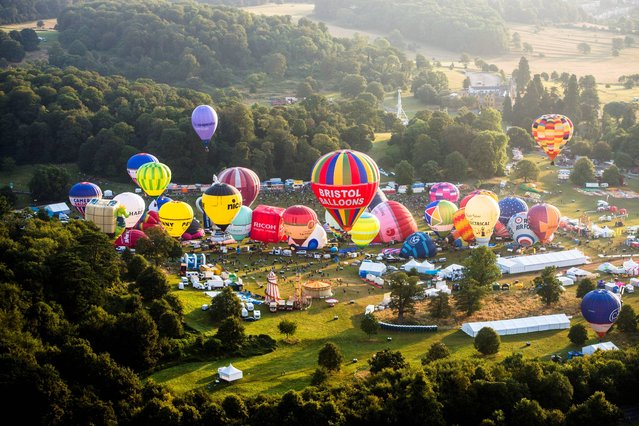 Hot air balloons lift off during a mass ascent at the 36th International Balloon Fiesta at the Ashton Court Estate near Bristol, which is Europe's largest ballooning event, on August 8, 2014. (Photo by Ben Birchall/PA Wire)