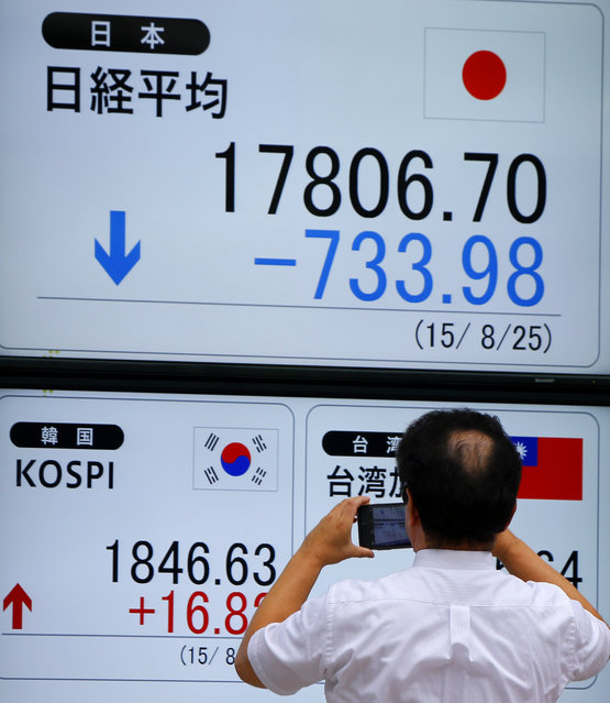 A man takes a photo of an electronic stock indicator of a securities firm in Tokyo, Tuesday, August 25, 2015. On Tuesday, Japan's main share index, the Nikkei 225, sank 4 percent to 17,806.70 in a session that saw the benchmark swing between positive and negative territory. It fell 4.6 percent on Monday. (Photo by Shizuo Kambayashi/AP Photo)