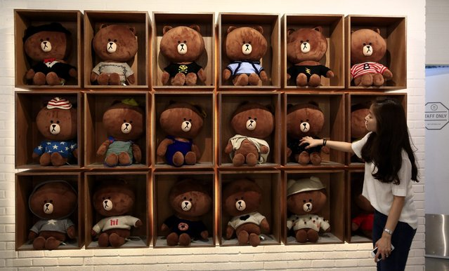 "A visitor looks at stuffed toys of ""Brown"", a character from the Line Corp. messaging application, at a Line Friends flagship store in the Itaewon district of Seoul, South Korea, 15 July 2016. (Photo by Jeon Heon-Kyun/EPA)"