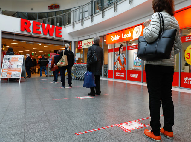 People wait to enter a shop, behind red lines that mark the distance customers have to keep between them, at a Rewe grocery store in Potsdam, Germany, March 20, 2020, as the spread of the coronavirus disease (COVID-19) continues. (Photo by Michele Tantussi/Reuters)