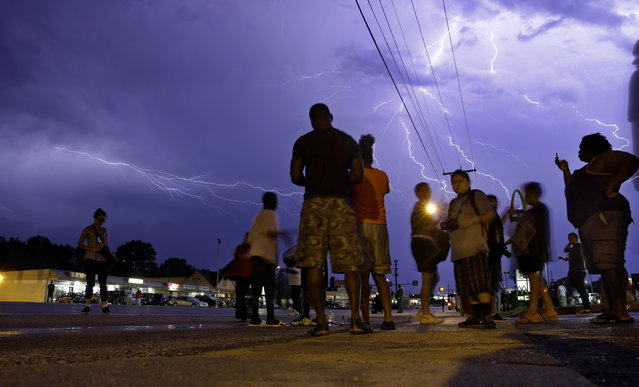 Protesters stand in the street as lightning flashes in the night sky in Ferguson, Mo. on Wednesday, August 20, 2014. A grand jury has begun hearing evidence as it weighs possible charges against the Ferguson police officer who fatally shot 18-year-old Michael Brown. (Photo by Jeff Roberson/AP Photo)