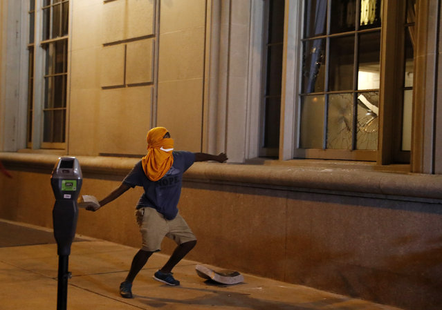 A man throws a rock into the window as demonstrators march in response to a not guilty verdict in the trial of former St. Louis police officer Jason Stockley, Sunday, September 17, 2017, in St. Louis. Stockley was acquitted in the 2011 killing of a black man following a high-speed chase. (Photo by Jeff Roberson/AP Photo)