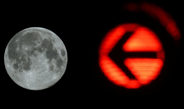 A traffic light is seen next to the Pink Supermoon in Frankfurt, Germany, April 8, 2020. (Photo by Kai Pfaffenbach/Reuters)