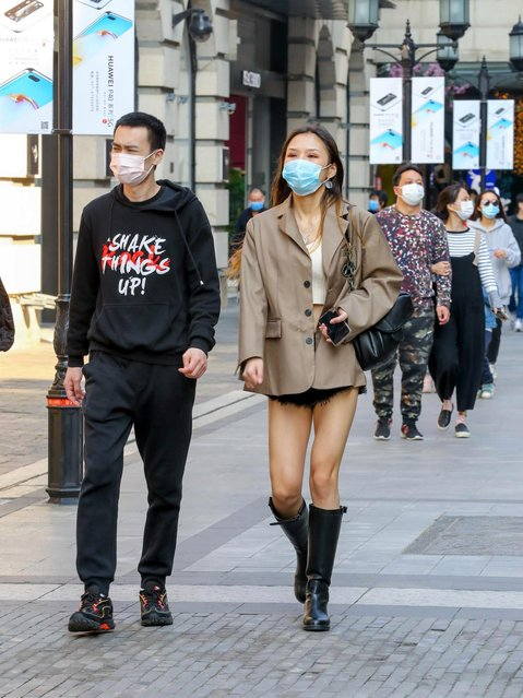 People wearing masks walk at a commercial pedestrian street following the lifting of the city's 76-day lockdown on April 12, 2020 in Wuhan, Hubei Province of China. (Photo by Zhang Chang/China News Service via Getty Images)