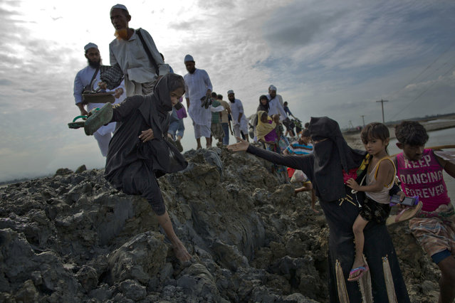 Rohingya Muslims walk towards a camp for refugees after crossing the boder from Myanmar into Bangladesh in Teknaf, Friday, September 29, 2017. More than a month after Myanmar's refugees began spilling across the border, the U.N. says more than half a million have arrived. (Photo by Gemunu Amarasinghe/AP Photo)