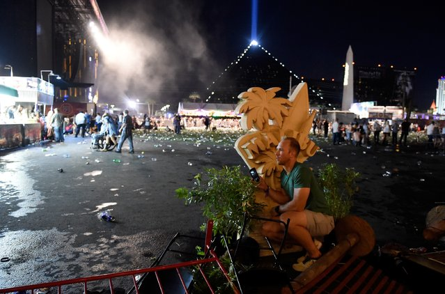 A person takes cover at the Route 91 Harvest country music festival after apparent gun fire was heard on October 1, 2017 in Las Vegas, Nevada. There are reports of an active shooter around the Mandalay Bay Resort and Casino. (Photo by David Becker/Getty Images)