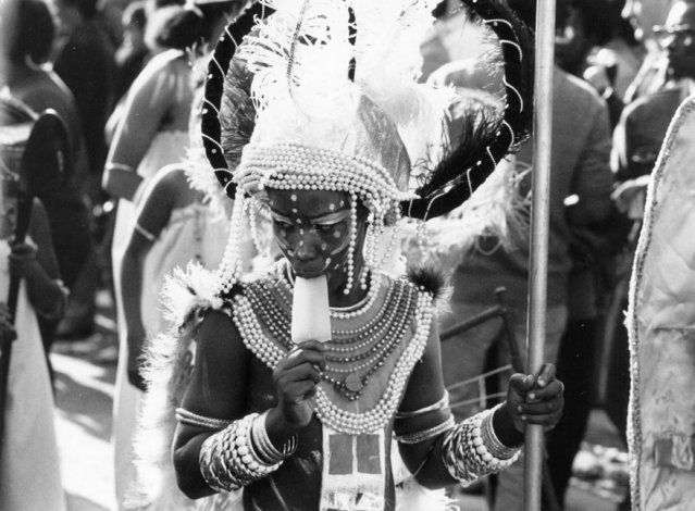 Sucks. A carnival participant sucks on an ice lolly during the parade at the Notting Hill Carnival, circa 1980. (Photo by Evening Standard)