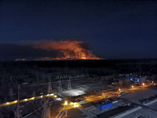 In this photo taken from the roof of Ukraine's Chernobyl nuclear power plant late Friday April 10, 2020, a forest fire is seen burning near the plant inside the exclusion zone.  Ukrainian firefighters are labouring to put out two forest blazes in the area around the Chernobyl nuclear power station that was evacuated because of radioactive contamination after the 1986 explosion at the plant. (Photo by Ukrainian Police Press Office via AP Photo)