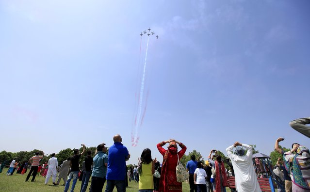 Spectators watch a performance by Pakistani jets during a ceremony marking Pakistan Defence Day in Islamabad, Pakistan, September 6, 2015. Pakistanis are celebrating the golden jubilee of Pakistan Defence Day in memory of the martyrs of the 1965 war who defended the motherland against the powerful Indian Army in the Indo-Pak war. (Photo by Faisal Mahmood/Reuters)