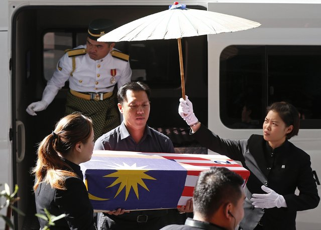 Lt Lee Vee Weng (C) carries the remains of his one-year-old son Benjamin Lee Jian Han, who was killed in the MH17 crash, into the Xiao En Bereavement Centre in Kuala Lumpur September 9, 2014. Malaysia Airlines (MAS) Flight MH17 crashed after being shot down over war-torn Ukraine on July 17, killing all 298 people on board. (Photo by Olivia Harris/Reuters)