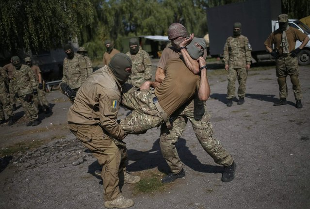 "Members of Ukrainian police special task force ""Sich"" take part in a drill at their base in Slaviansk September 15, 2014. Fighting broke out again in Ukraine's rebel-held city of Donetsk on Monday as President Petro Poroshenko prepared to unveil a risky plan to give the separatist-minded east ""special status"" in a bid to end a conflict that has killed over 3,000 people. (Photo by Gleb Garanich/Reuters)"