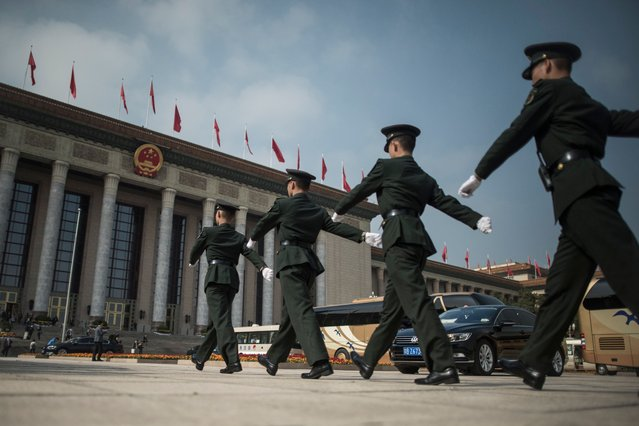 Chinese paramilitary guards walk in front of the Great Hall of the People during the Communist Party's 19th Congress in Beijing on October 19, 2017. The Chinese Communist Party opens its week-long, twice-a-decade congress in the Great Hall of the People. (Photo by Fred Dufour/AFP Photo)