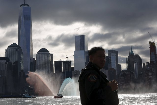 A Jersey City Fire Department boat throws water with the colors red, blue, and white along the Hudson river while a New Jersey police officer stands guard during a ceremony for 9/11 victims at a memorial, across from New York's Lower Manhattan and One World Trade Center in Exchange Place, New Jersey September 11, 2015. (Photo by Eduardo Munoz/Reuters)