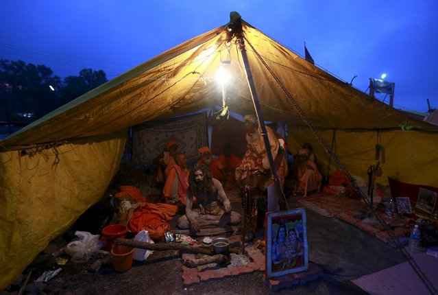 "Sadhus, or Hindu holy men, sit inside their tent during the second ""Shahi Snan"" (grand bath) at ""Kumbh Mela"", or Pitcher Festival, in Trimbakeshwar, India, September 13, 2015. (Photo by Danish Siddiqui/Reuters)"