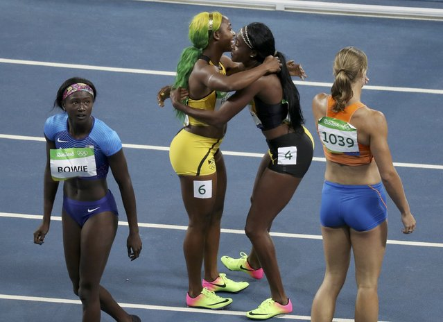 2016 Rio Olympics, Athletics, Final, Women's 100m Final, Olympic Stadium, Rio de Janeiro, Brazil on August 13, 2016. Shelly Ann Fraser-Pryce (JAM) (2nd-L) of Jamaica, winner of the bronze medal, is embraced by gold medal winner Elaine Thompson (JAM) of Jamaica  after the women's 100 meters. (Photo by Carlos Barria/Reuters)