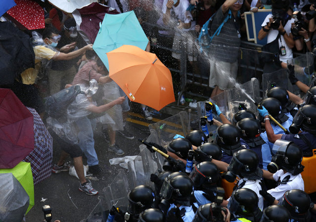 Protesters wearing raincoats and carrying umbrellas face pepper spray from riot police, as tens of thousands of protesters block the main street to the financial Central district outside the government headquarters in Hong Kong September 28, 2014. (Photo by Bobby Yip/Reuters)