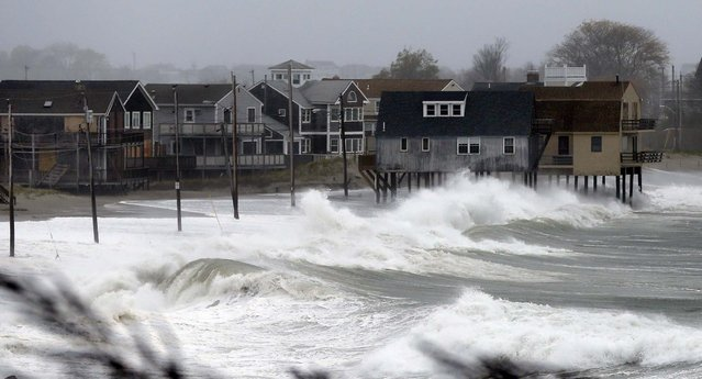 Ocean waves kick up near homes along Peggoty Beach in Scituate, Massachusetts on Monday. (Photo by Elise Amendola/Associated Press)