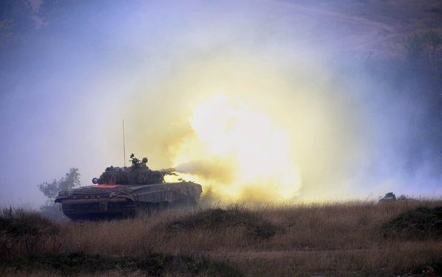 """A Soviet made Hungarian T-72 main battle tank shoots during a joint Hungarian-US military exercise near Osku village, Hungary on October 2, 2014. The six-week exercise titled """"Joint Action 2014″ with 1300 soldiers taking part, takes place from September 8 and October 17, 2014. (Photo by Attila Kisbenedek/AFP Photo)"""