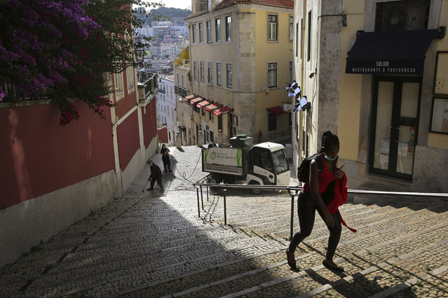 In this photo taken Wednesday, June 24, 2020, a woman wearing a face mask walks past workers washing the street in Lisbon's old center. Portugal avoided the dramatic numbers of infections and deaths recorded by some other European Union countries during the early months of the coronavirus outbreak but since ending its state of emergency and lockdown at the end of April, its total of officially recorded new infections has remained stubbornly high. (Photo by Armando Franca/AP Photo)