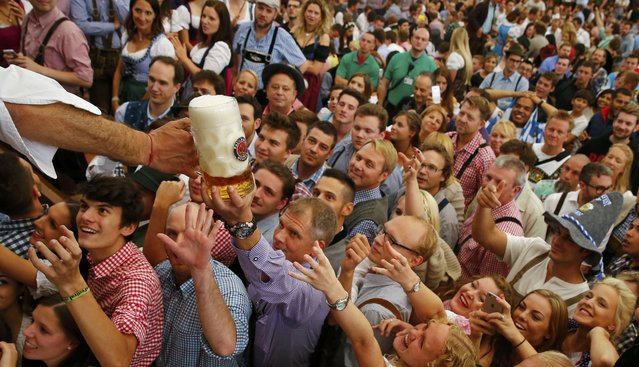 Visitors reach for one of the mugs of beer from the first barrel during the opening ceremony for the 182nd Oktoberfest in Munich, Germany, September 19, 2015. (Photo by Michael Dalder/Reuters)