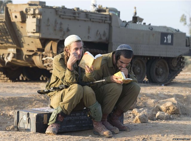 Israeli soldiers conduct morning prayers at an Israeli army deployment area near the Israel-Gaza Strip border as they prepare for a potential ground operation in the Palestinian coastal enclave on November 20, 2012. (Photo by Jack Guez/AFP Photo)