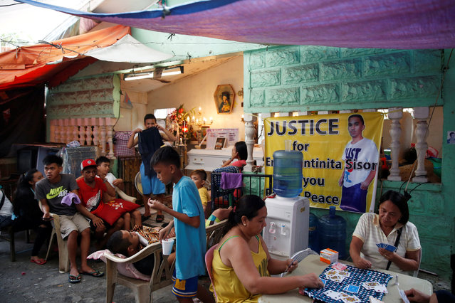 """Relatives and friends play cards and gather at the wake of Eric Quintinita Sison in Pasay city, Metro Manila in the Philippines August 29, 2016. Family members of Sison said he was attempting to surrender when he was gunned down by the police during a recent """"Meth"""" buy bust operation in Pasay city. (Photo by Erik De Castro/Reuters)"""