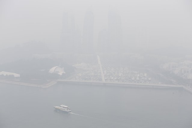 A yacht passes a marina next to a luxury condominium project shrouded by haze in Singapore September 29, 2015. (Photo by Edgar Su/Reuters)