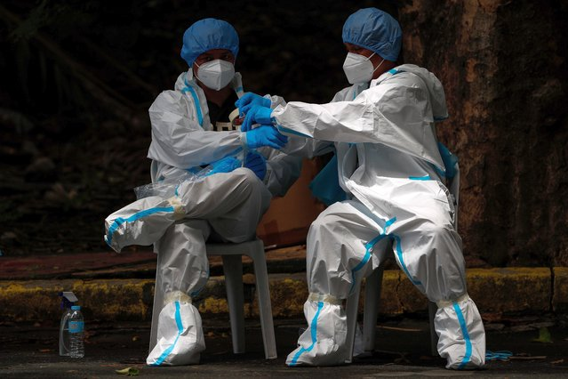 Health workers secure their personal protective equipment (PPEs) before their shift at a swabbing facility in Quezon City, northeast of Manila, Philippines, 30 July 2020. A mass swab test for delivery riders and government workers was held in Quezon City as members of the Inter-Agency Task Force on Emerging Infectious Diseases (IATF-EID) held a press conference discussing how to prevent further spreading of COVID-19 amid the ongoing coronavirus pandemic. (Photo by Mark R. Cristino/EPA/EFE)