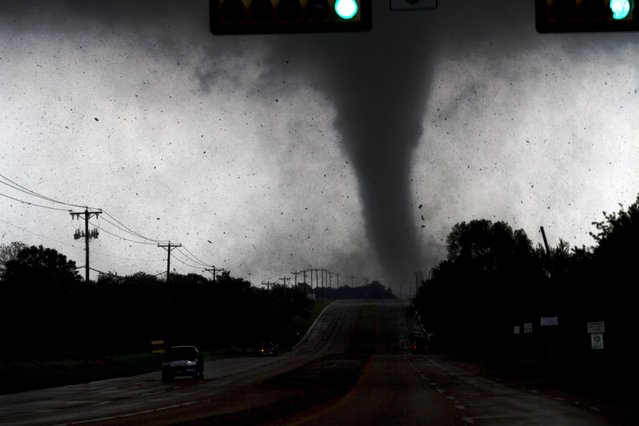 In this April 3, 2012 file photo, a tornado touches down in Lancaster, Texas, south of Dallas. Tornadoes tore through the Dallas area, peeling roofs off homes, tossing big-rig trucks into the air and leaving flattened tractor trailers strewn along highways and parking lots. (Photo by Parrish Velasco/AP Photo/The Dallas Morning News)