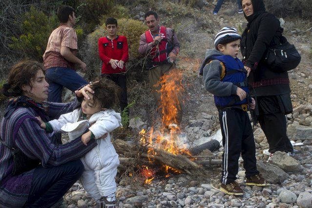 Afghan refugees try to warm next to a fire following their arrival on an overcrowded dinghy in rough sea on the Greek island of Lesbos, after crossing a part of the Aegean Sea from the Turkish coast, October 2, 2015. (Photo by Dimitris Michalakis/Reuters)