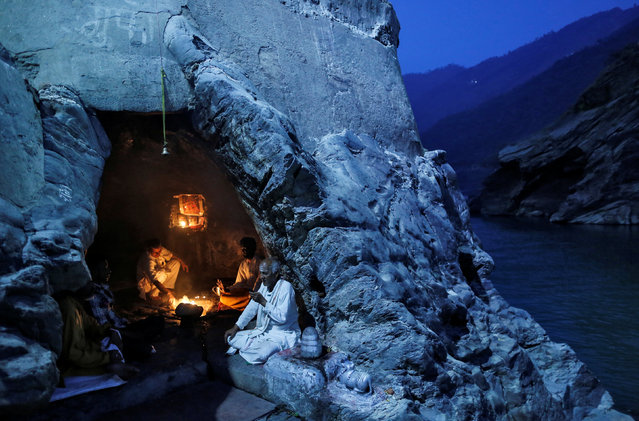 Hindu priests sit inside a cave as they perform evening prayers on the banks of the river Ganges in Devprayag, India, March 28, 2017. (Photo by Danish Siddiqui/Reuters)