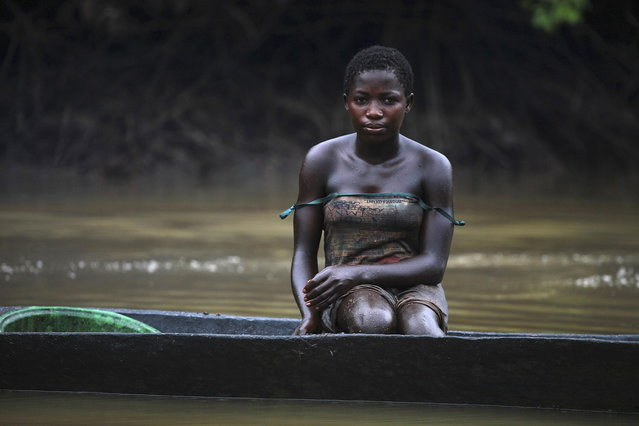 A young woman named Akpomene is pictured coated in oil stains as she sits in a canoe near river Nun in Nigeria's oil state of Bayelsa November 27, 2012. Akpomene fishes in the creek and sells the fish to help her family. She washes after fishing but has sticky rashes on her body. (Photo by Akintunde Akinleye/Reuters)