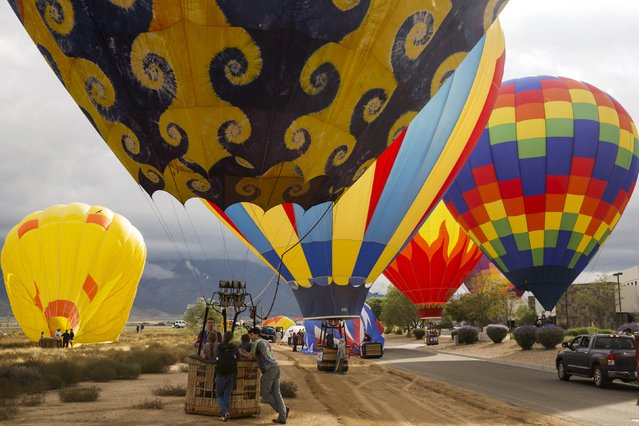 Crew members work to secure a hot air balloon after landing during the 2015 Albuquerque International Balloon Fiesta in Albuquerque, New Mexico, October 4, 2015. (Photo by Lucas Jackson/Reuters)