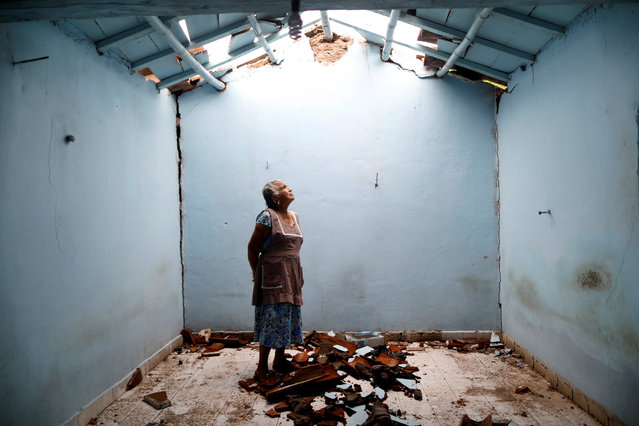"""Tomasa Mozo, 69, a housewife, looks up at the roof as she poses for a portrait inside the ruins of her house after an earthquake in San Jose Platanar, at the epicenter zone, Mexico, September 28, 2017. The house was badly damaged but with the help of her family Mozo rescued some furniture. She lives in another room of her house and hopes to repair the damage as soon as possible. """"I'm afraid to go out, I can not sleep"""", Mozo said. (Photo by Edgard Garrido/Reuters)"""