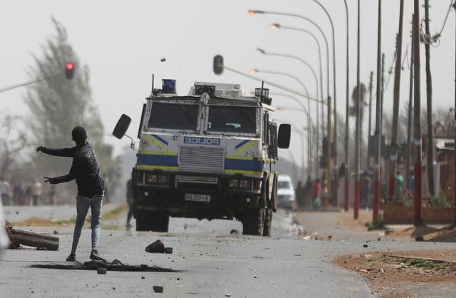 A man throws a stone at a police Inyala (armoured vehicle) during a protest demanding the police account for the death of the teenage boy who was allegedly shot by the police the previous night in Eldorado park, outside Johannesburg, South Africa on August 27, 2020. (Photo by Siphiwe Sibeko/Reuters)
