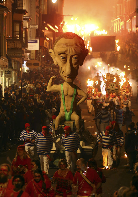 An effigy of Russian President Vladimir Putin is paraded through the town of Lewes, England, where an annual bonfire night procession is held by the Lewes Bonfire Societies, Wednesday November 5, 2014. (Photo by Gareth Fuller/AP Photo/PA Wire)
