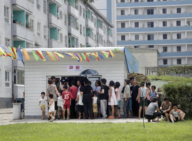 In this August 16, 2015 photo, people queue up at kiosk in Pyongyang, North Korea. Street stalls that offer North Koreans a place to spend – or make – money on everything from snow cones to DVDs are flourishing in Pyongyang and other North Korean cities, modest but growing forms of private commerce in a country where capitalism is officially anathema. (Photo by Dita Alangkara/AP Photo)